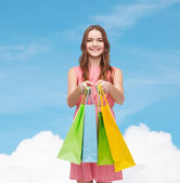 Smiling woman in dress with many shopping bags — Stock Photo