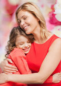 Smiling mother and daughter hugging — Stock Photo