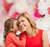 Smiling mother and daughter whispering gossip — Stock Photo