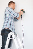 Man with electric drill making hole in wall — Stok fotoğraf
