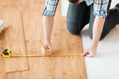 Close up of male hands measuring wood flooring — Stok fotoğraf