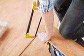 Close up of male hands cutting parquet floor board — Stock Photo