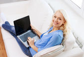Smiling woman with laptop computer at home — Stock Photo