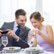 Smiling couple with appetizers and smartphones — Stock Photo #43821099