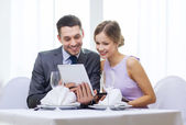 Couple with menus on tablet pc at restaurant — Stock Photo