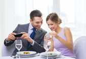 Smiling couple with appetizers and smartphones — Stock Photo