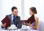 Smiling couple with menus at restaurant — Stock Photo