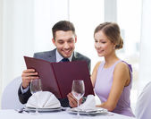 Smiling couple with menu at restaurant — Stok fotoğraf