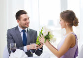Smiling man giving flower bouquet at restaurant — Stock Photo