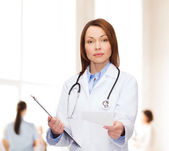Calm female doctor with clipboard — Stock Photo