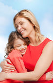 Smiling mother and daughter hugging — Photo