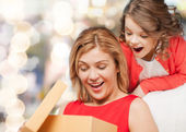 Smiling mother and daughter with gift box — Foto de Stock