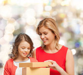 Smiling mother and daughter with gift box — Stock fotografie