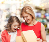 Smiling mother and daughter opening gift box — Stok fotoğraf