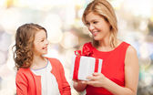 Smiling mother and daughter with gift box — Stockfoto