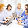 Smiling team with laptop and table pc computers — Stock Photo