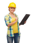 Smiling woman in helmet with clipboard — Foto de Stock