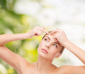Young woman squeezing acne spots — Stock Photo