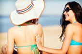 Girls applying sun cream on the beach — Stock Photo