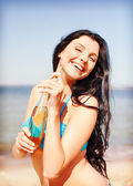 Girl with bottle of drink on the beach — Stok fotoğraf