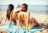 Girls sunbathing on the beach — Stok fotoğraf
