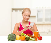 Woman with vegetables pointing at smartphone — Stock Photo