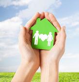 Manos sosteniendo una casa verde con familia — Foto de Stock
