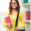 Smiling female student with bag and notebooks — 图库照片