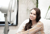 Happy and smiling woman sitting near ventilator — Stock Photo