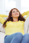 Smiling young woman lying on sofa at home — Stock Photo