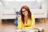 Smiling student girl reading books at home — Stock Photo