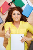 Smiling female student with textbook and pencil — Stock Photo