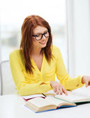 Smiling student girl reading books in college — Stock Photo
