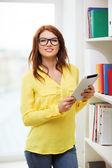 Lächelnd studentin mit tablet-pc in der bibliothek — Stockfoto