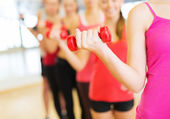 Group of people working out with dumbbells in gym — Stock Photo