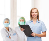 Smiling female doctor or nurse with clipboard — Stock Photo