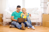 Couple with laptop sitting on floor in new house — Stock Photo