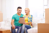 Couple relaxing on sofa with tablet pc in new home — Stock Photo