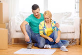 Smiling couple looking at bluepring in new home — Stock Photo