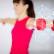Sporty woman hands with light red dumbbells — Stock Photo