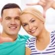 Smiling happy couple making frame gesture at home — Stock Photo