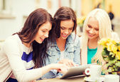 Beautiful girls looking at tablet pc in cafe — Stock Photo