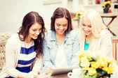 Piękne dziewczyny, patrząc na tablet w kawiarni — Zdjęcie stockowe