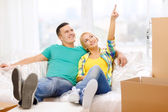 Smiling couple relaxing on sofa in new home — Stockfoto