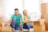 Smiling couple unpaking boxes with kitchenware — Stockfoto