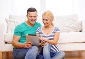 Lachende gelukkige paar met de tablet pc thuis — Stockfoto