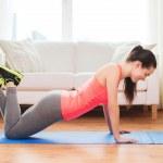 Smiling teenage girl doing push-ups at home — Stock Photo #44454457
