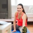 Smiling teenage girl streching on floor at home — Stock Photo #44454711
