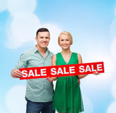 Smiling couple with sale sign — Stock Photo
