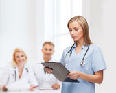女性医師や看護師のクリップボードと笑みを浮かべてください。 — ストック写真